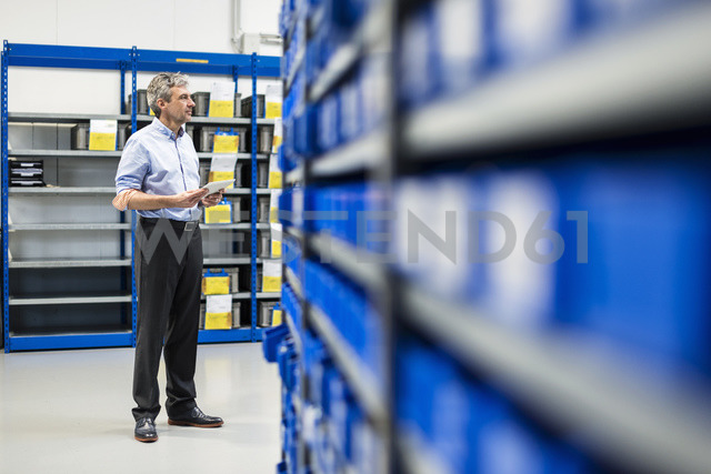 Businessman using tablet in production hall - DIGF03499