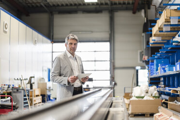 Businessman using tablet in production hall - DIGF03505