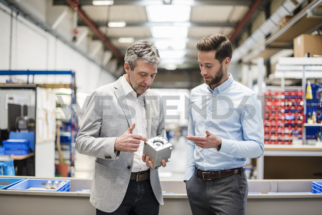 Businessmen during meeting with a product in production hall - DIGF03508