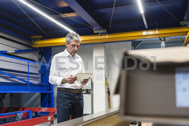 Businessman using tablet in production hall - DIGF03514 - Daniel Ingold/Westend61