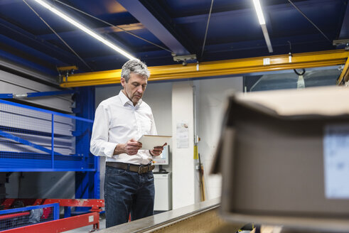 Businessman using tablet in production hall - DIGF03514