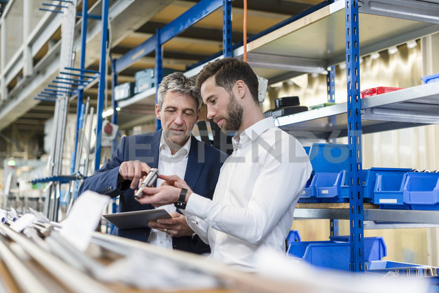 Businessmen during meeting with tablet and product in production hall - DIGF03523 - Daniel Ingold/Westend61