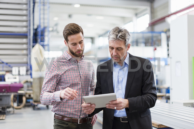 Businessmen using tablet during meeting in production hall - DIGF03541