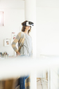 Woman wearing VR glasses at home - MOEF00926