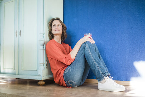 Relaxed woman sitting on the floor at home - MOEF00929