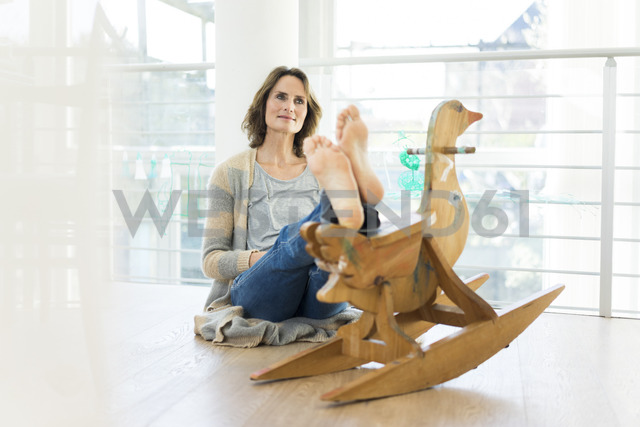Barefoot woman sitting on the floor at homewith wooden toy - MOEF00932