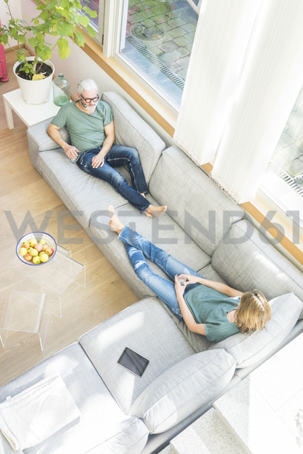 Mature couple relaxing on couch at home - MOEF00935