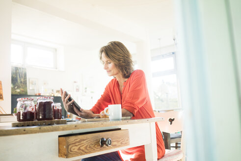 Woman with tablet and homemade strawberry jam at home - MOEF00941