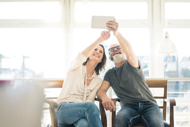 Happy mature couple sitting on chairs at home using tablet - MOEF00944