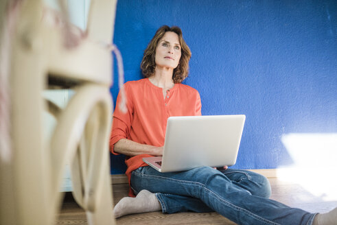 Woman sitting on the floor at home with laptop - MOEF00947