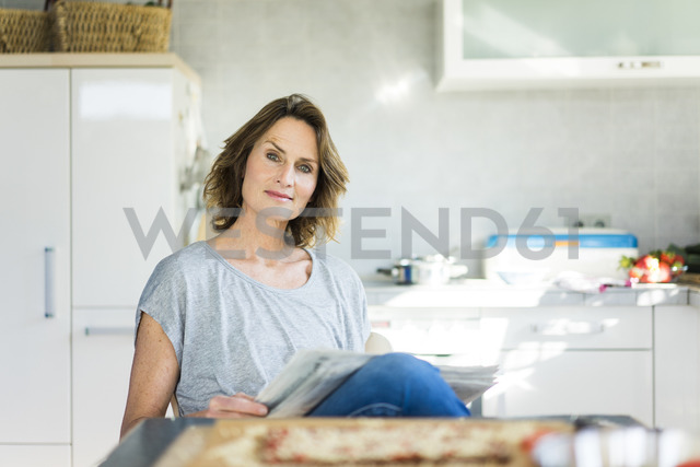 Portrait of woman with newspaper in kitchen at home - MOEF00950