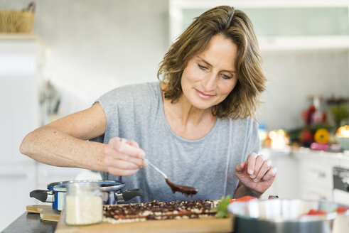 Woman making strawberry chocolate in kitchen at home - MOEF00953