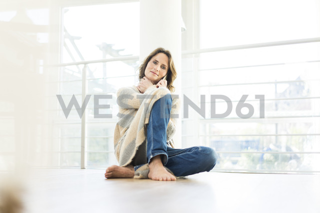 Portrait of relaxed woman sitting on the floor at home - MOEF00962