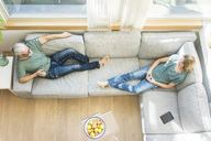 Mature couple relaxing on couch at home - MOEF00965