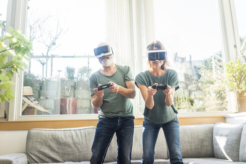 Mature couple in kiving room at home wearing VR glasses playing video game - MOEF00968