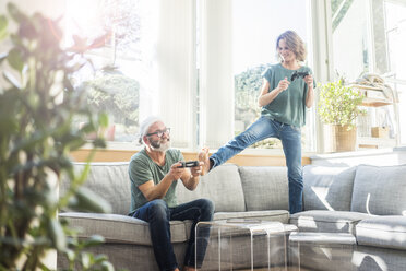 Happy mature couple on couch at home playing video game - MOEF00971