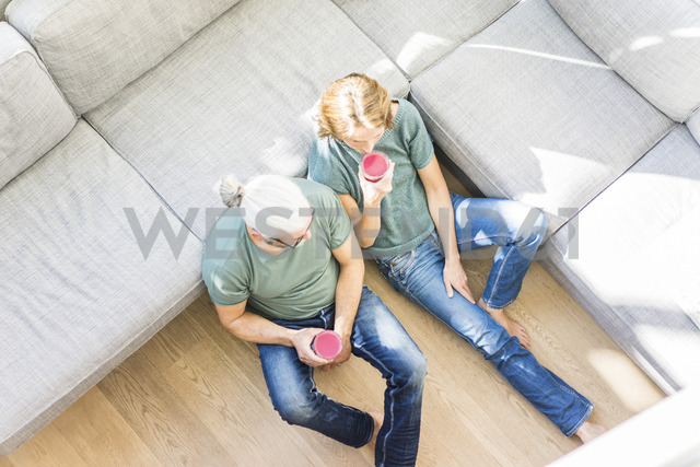 Mature couple with healthy drinks in living room at home - MOEF00974
