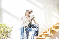 Portrait of smiling mature couple standing on stairs at home - MOEF00980