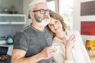 Mature couple drinking coffee in kitchen at home - MOEF00983