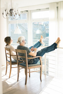 Relaxed mature couple sitting on chairs at home with feet up - MOEF00989