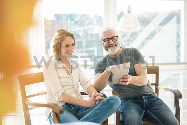 Happy mature couple sitting on chairs at home using tablet - MOEF00992