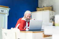 Frustrated Santa using laptop at home - MOEF00995