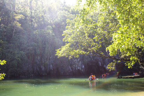 Hikers on boats moving towards cave - CAVF24892