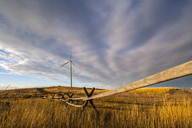Windmills and wooden fence on field against cloudy sky - CAVF24919