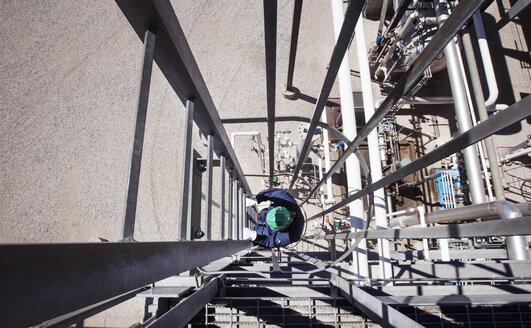 Overhead view of worker climbing staircase at power station - CAVF25015