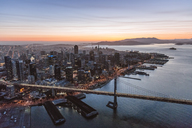 Aerial view of Oakland Bay Bridge over sea by city during sunset - CAVF25024