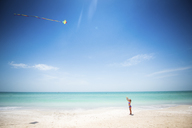 Girl flying kite at beach against sea and sky - CAVF25060