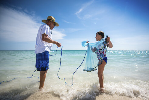 Grandfather holding rope of fishing net carried by granddaughter while standing on shore at beach against sky - CAVF25066