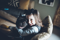 High angle portrait of happy girl embracing French Bulldog while sitting sofa at home - CAVF25093