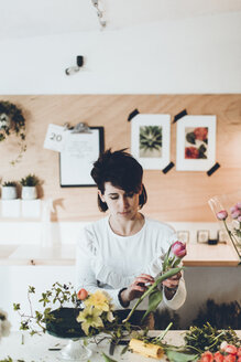 Florist working at table in flower shop - CAVF25096