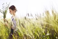 Side view of female farmer holding wheat plants on field - CAVF25114