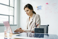 Businesswoman using laptop computer while sitting against whiteboard in office - CAVF25210