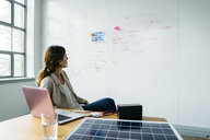 Businesswoman looking at diagram on whiteboard while working over solar panel in office - CAVF25213
