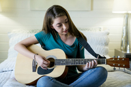 Teenage girl plucking guitar in bedroom - CAVF25321