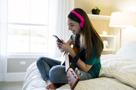 Side view of teenage girl using smart phone while sitting with guitar in bedroom - CAVF25324