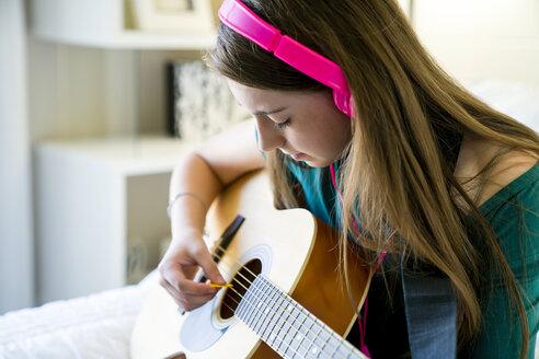 Teenage girl playing guitar in bedroom - CAVF25327