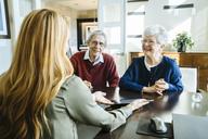 Female financial advisor explaining plan to senior couple on tablet computer in office - CAVF25354