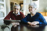 Cropped image of financial advisor explaining plan to senior couple on tablet computer in office - CAVF25357