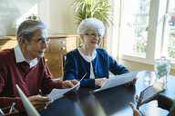 Senior couple reading documents while discussing with financial advisor in office - CAVF25360
