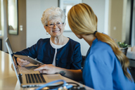 Happy senior woman looking at home caregiver while holding tablet computer - CAVF25384