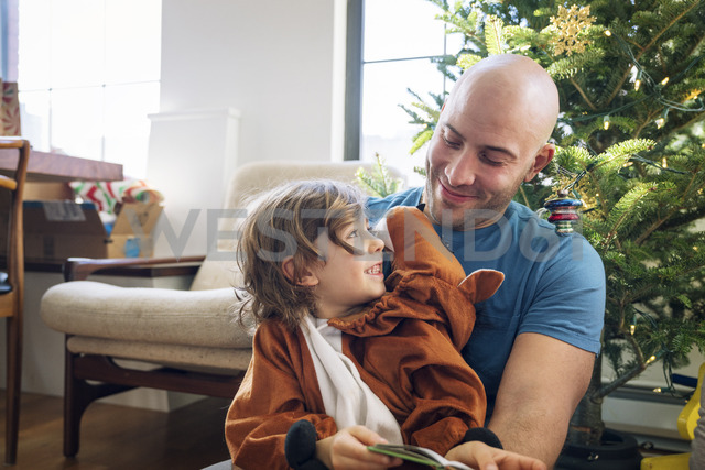 Happy father looking at son dressed in costume against Christmas tree at home - CAVF25438