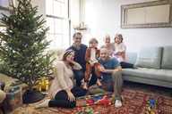 Portrait of smiling family by Christmas tree at home - CAVF25441