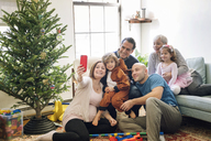 Pregnant woman taking selfie while sitting with family by Christmas tree at home - CAVF25444
