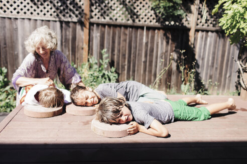 Grandmother looking at grandson lying with brothers on floorboard in yard during sunny day - CAVF25480