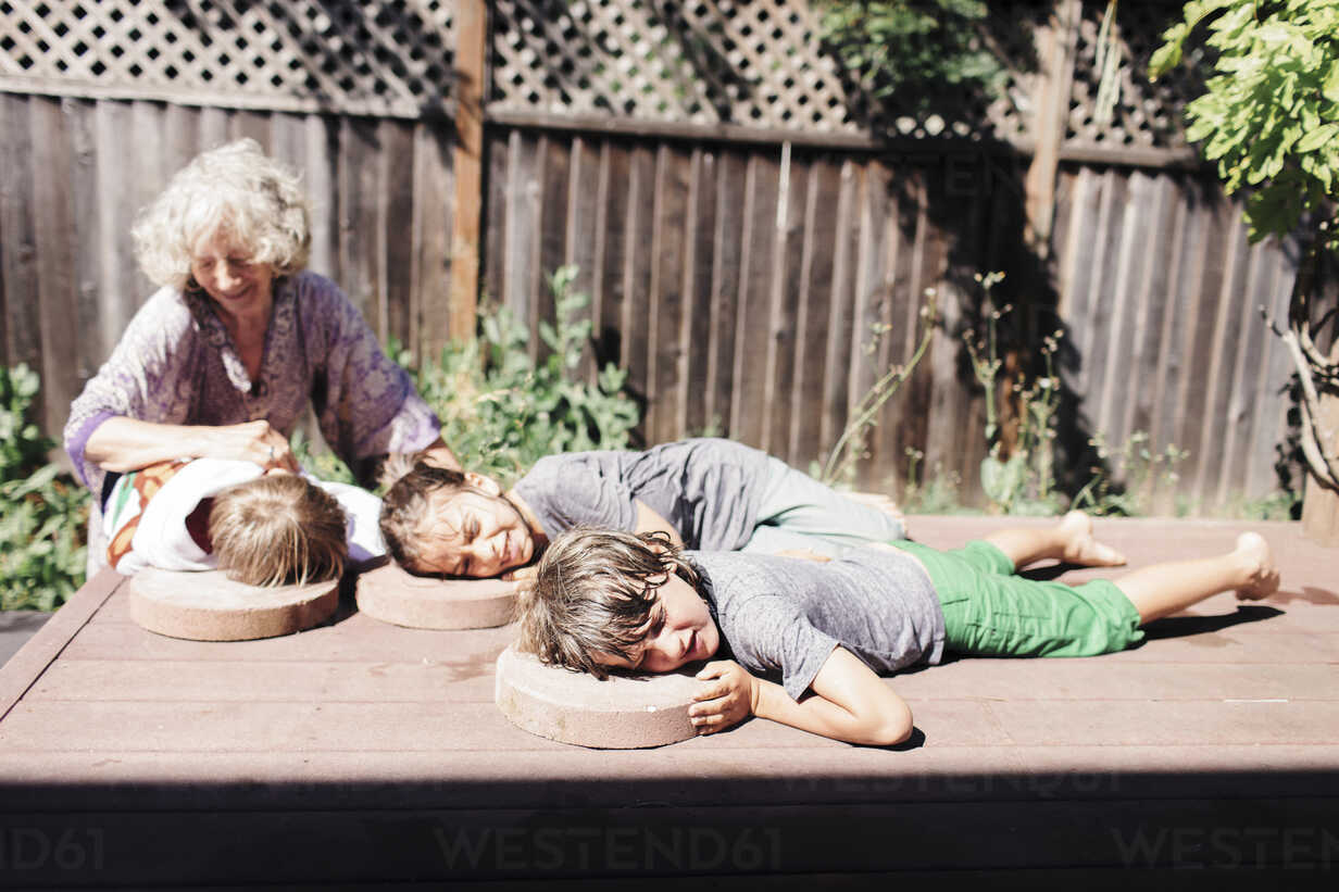 Grandmother looking at grandson lying with brothers on floorboard in yard during sunny day - CAVF25480 - Cavan Images/Westend61