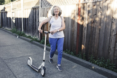 Portrait of confident senior woman walking with push scooter in yard - CAVF25489